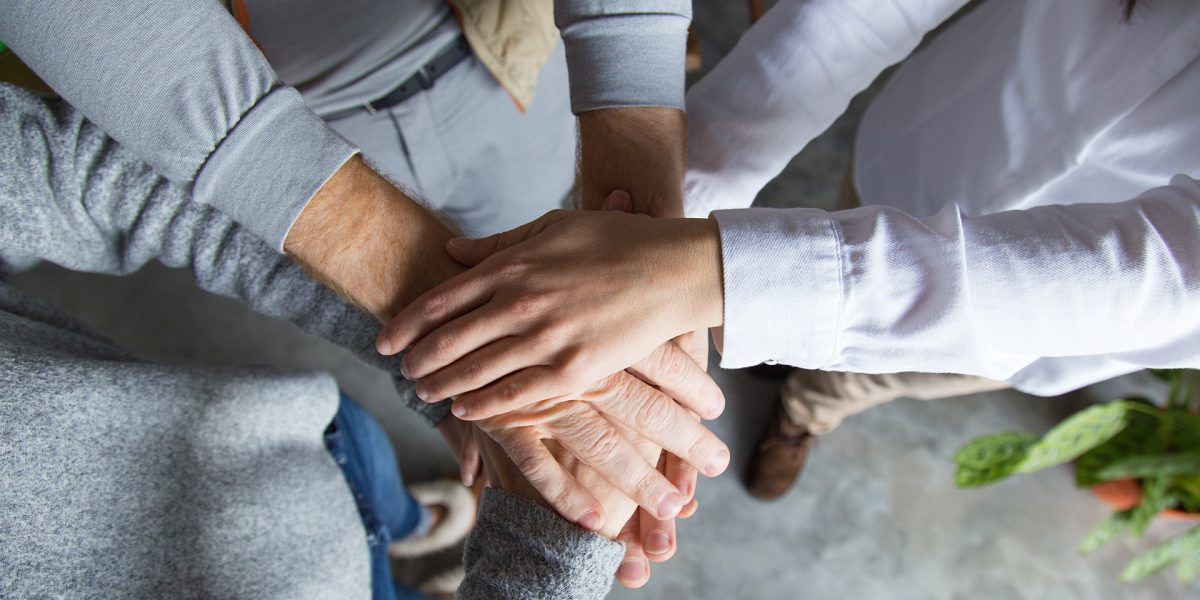 Three people expressing friendship. Top view of stack of hands. Teamwork or support concept